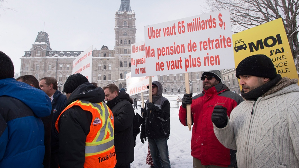 Taxi drivers demonstrate as a legislature committee studies the legality of Uber, at the legislature in Quebec City, Thursday, Feb. 18, 2016. (Jacques Boissinot / THE CANADIAN PRESS)