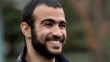 Omar Khadr smiles as he speaks to the media
