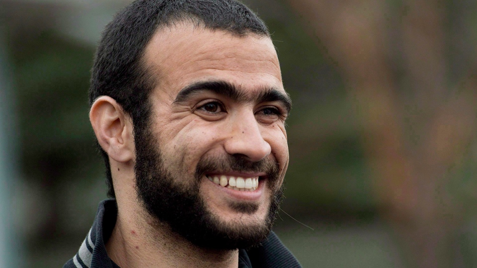 Omar Khadr smiles as he speaks to the media