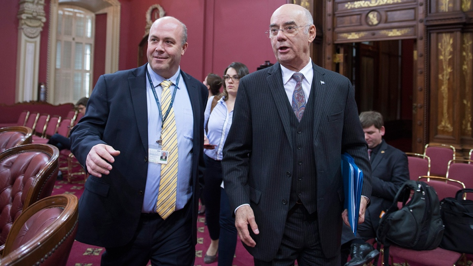Quebec Transport Minister Jacques Daoust, right, arrives at a legislature committee studying the taxi industry and Uber, Thursday, Feb. 18, 2016 at the legislature in Quebec City. (Jacques Boissinot / THE CANADIAN PRESS)