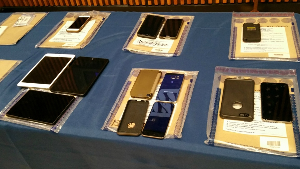 A collection of Apple iPhones and iPads fill a table during a news conference at New York City Police Headquarters in New York on Thursday, Feb. 18, 2016. (AP / Verena Dobnik)
