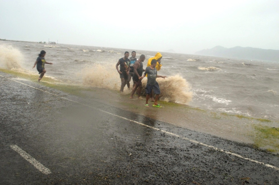 People are splashed by a wave whipped up by the encroaching cyclone Winston in Labasa, Fiji, Saturday, Feb. 20, 2016. (Luke Rawalai/Fiji Times via AP)