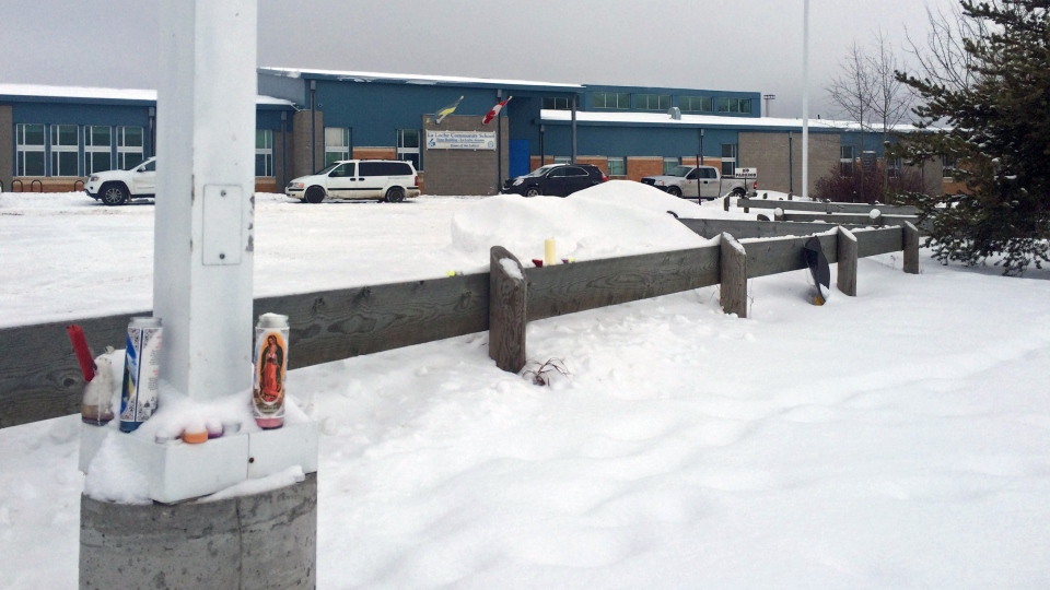 Snow-covered candles remain outside the Saskatchewan school where a deadly shooting took place on Jan. 22.