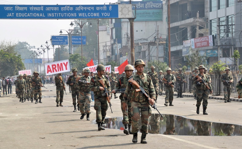 Indian army soldiers conduct a flag march at Rohtak, after Friday was rocked with violence in Haryana state, India, Saturday, Feb. 20, 2016. (Deepak Khanna via AP)