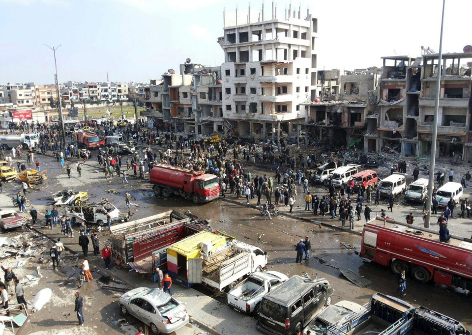 In this photo released by the Syrian official news agency SANA, Syrian citizens gather at the scene where two blasts exploded in the pro-government neighborhood of Zahraa, in Homs province, Syria, Sunday, Feb. 21, 2016. (SANA via AP)