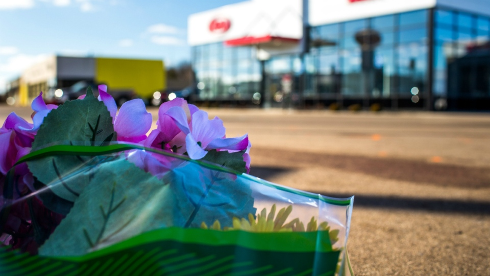 Flowers rest in the parking lot of a car dealership in Kalamazoo, Mich. on Sunday, Feb. 21, 2016. (Andraya Croft / Detroit Free Press)