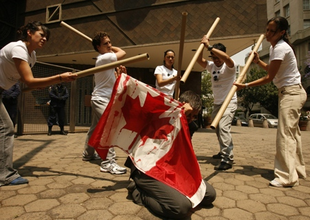 An actor playing the part of a Canadian embassy employee, covers himself with a bloodied Canadian flag as other beat him with cardboard tubes during a protest in front of the Canadian embassy in Mexico city, Thursday, March 29, 2007. (AP / Dario Lopez-Mills)