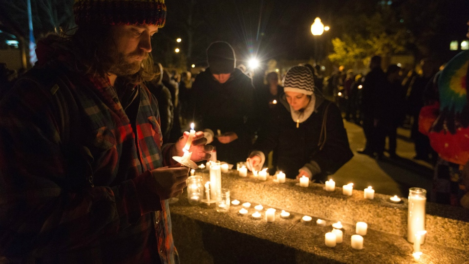 Joe Lucido lights a candle during the candlelight vigil at Bronson Park in remembrance of the mass shooting victims in Kalamazoo, Mich. on Monday, Feb. 22, 2016. (Bryan Bennett / Kalamazoo Gazette-MLive Media Group)