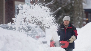 Bill Aikman clears snow from in front of his neighbour's house as he digs out from a winter storm in Ottawa, Wednesday, Feb. 17, 2016. (Adrian Wyld / THE CANADIAN PRESS)