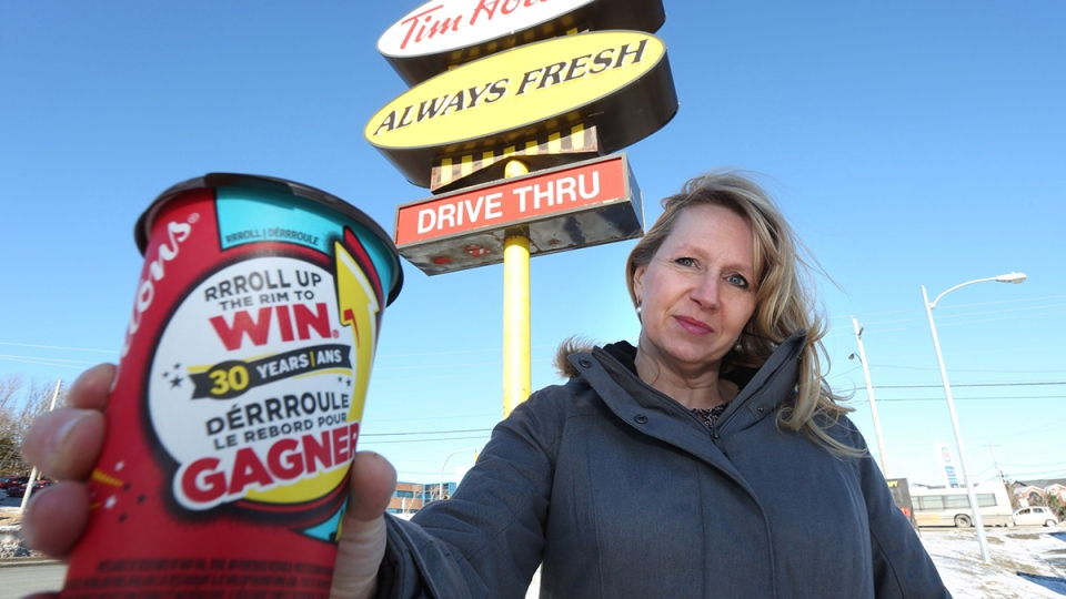 Margaret Coward holds a coffee cup outside the Tim Hortons on Portugal Cove Road in St. John's, N.L. on Tuesday, Feb. 23, 2016. (Paul Daly / THE CANADIAN PRESS)