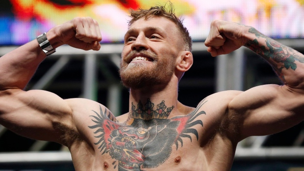 Conor McGregor poses on the scale during the weigh-in for UFC 194, Friday, Dec. 11, 2015, in Las Vegas. (AP Photo/John Locher)