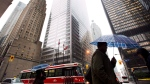 A man carries an umbrella through downtown Toronto during a rainstorm in this file photo. (Nathan Denette/The Canadian Press)