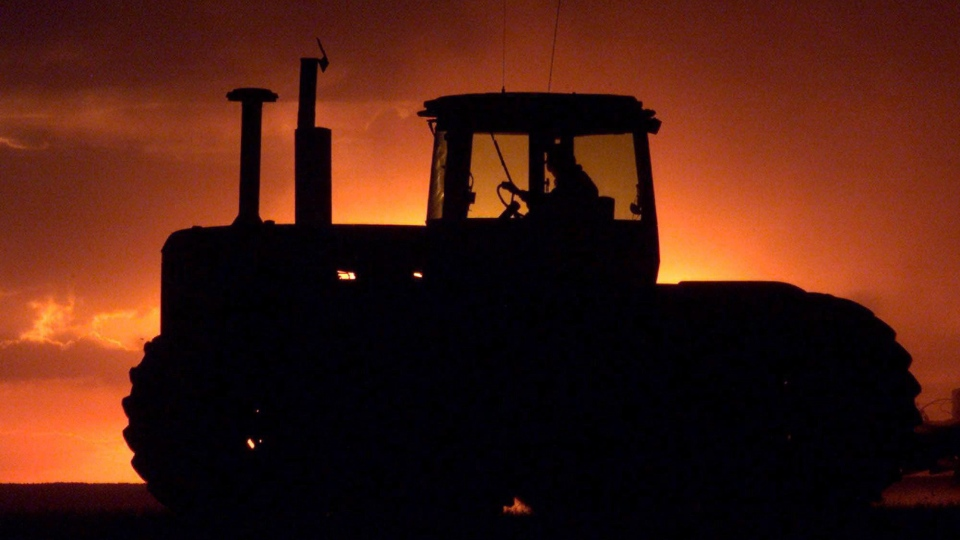 A farm tractor is silhouetted against a setting sun near Mossbank, Saskatchewan, Saturday May 11, 2002. (THE CANADIAN PRESS / Adrian Wyld)