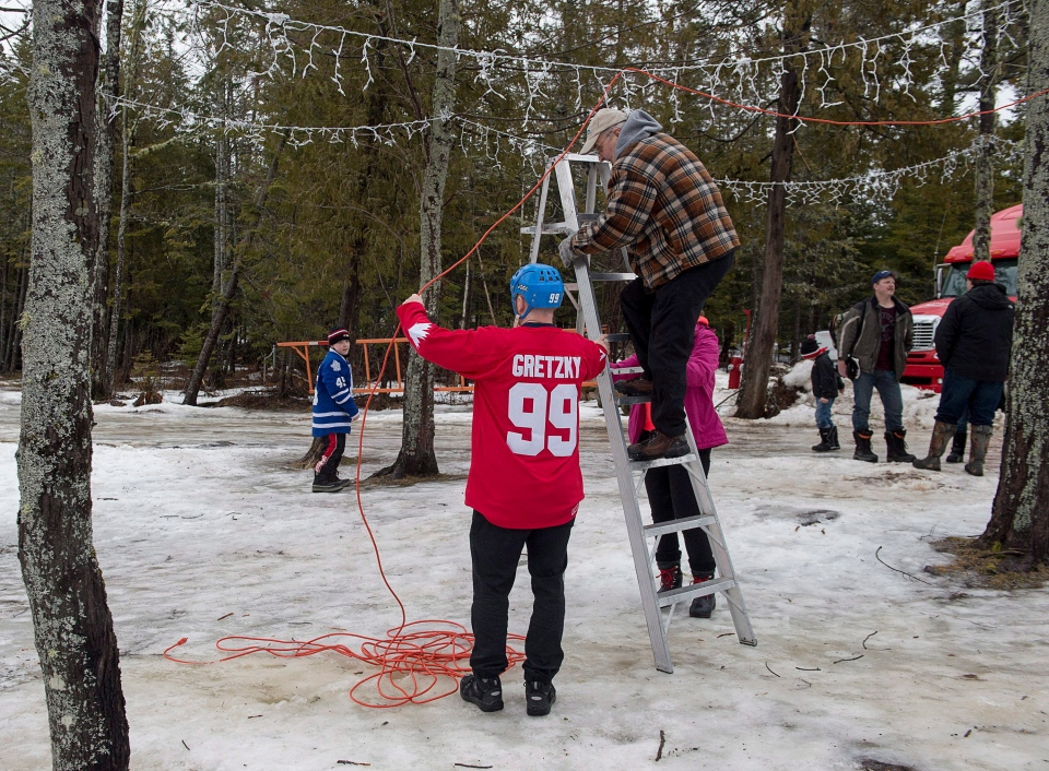 A fan wearing a Wayne Gretzky jersey helps a worker string a cable at the World Pond Hockey Championship, in Plaster Rock, N.B., on Thursday, Feb. 25, 2016. (Andrew Vaughan / THE CANADIAN PRESS)