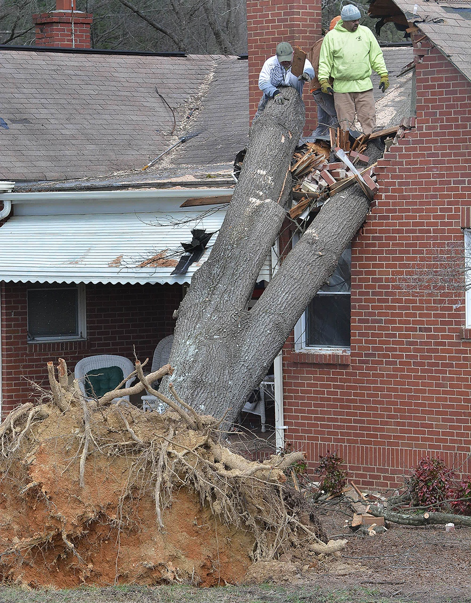 People remove debris from home in Durham, N.C., Thursday, Feb. 25, 2016. (Bernard Thomas / The Herald-Sun via AP)