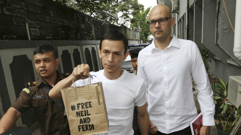 Canadian teacher Neil Bantleman, right, walks with Indonesian teaching assistant, Ferdinant Tjiong prior to the start of their trial hearing at South Jakarta District Court in Jakarta, Indonesia on Tuesday, Dec. 2, 2014. (AP / Tatan Syuflana)
