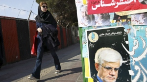 An Iranian woman walks past electoral posters of candidates of parliamentary elections in a sidewalk in Vanak square in northern Tehran, Iran, Thursday, Feb. 25, 2016. (AP / Vahid Salemi)