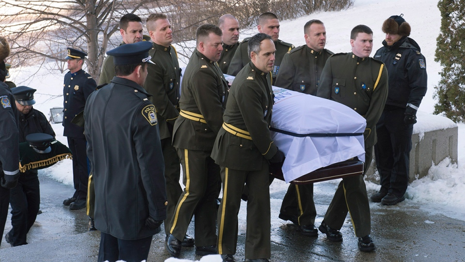 Surete du Quebec police officers carry the casket of police officer Thierry LeRoux, in Saguenay, Que.  on Friday, Feb. 26, 2016. (Jacques Boissinot / THE CANADIAN PRESS)