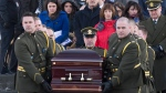 Joannie Vaillancourt, left, wife of Lac-Simon police officer Thierry LeRoux, and LeRoux's father Michel LeRoux follow the casket at the end of the funeral service for police officer Thierry LeRoux, in Saguenay, Que., Friday, Feb. 26, 2016. (Jacques Boissinot / THE CANADIAN PRESS)