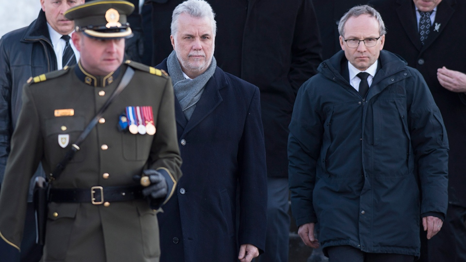 Quebec Premier Philippe Couillard, centre, and Quebec Public Security Minister and Municipal Affairs Minister Martin Coiteux, right, follow a police officer at the end of the funeral service of police officer Thierry LeRoux Friday, Feb. 26, 2016. (Jacques Boissinot / THE CANADIAN PRESS)