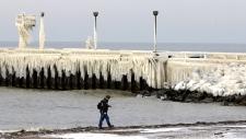 A man walks along the shores of Lake Erie