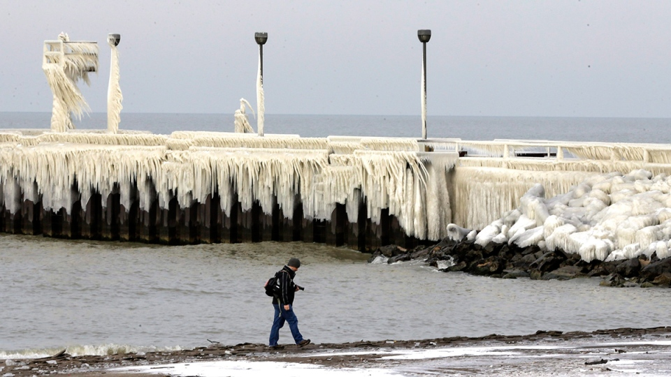 A man walks along the shores of Lake Erie past an ice covered pier at Wildwood Park, in Cleveland, Thursday, Jan. 14, 2016. (AP / Tony Dejak)