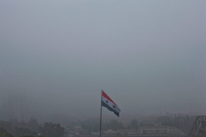 A Syrian national flag waves as heavy fog envelops the capital city of Damascus, Syria, Wednesday, Feb. 24, 2016. A top military official says Russia has halted all airstrikes in areas of Syria where armed groups, including government forces, said they would abide by a cease-fire. (AP Photo/Hassan Ammar)