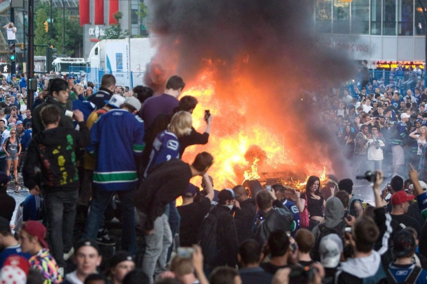 Vancouver Canucks fans watch a car burn during a riot following game 7 of the NHL Stanley Cup final in downtown Vancouver, B.C., on June 15, 2011. (Geoff Howe/THE CANADIAN PRESS)