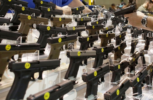 Customer looks at pistol at gun show
