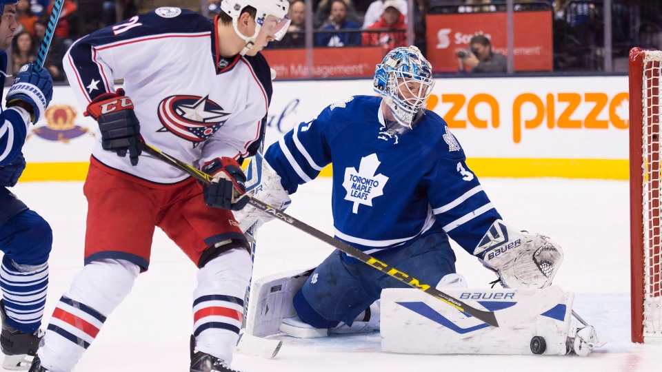 Toronto Maple Leafs goalie James Reimer (34) makes a save against Columbus Blue Jackets left wing Kerby Rychel (21) during first period NHL hockey action in Toronto on Wednesday, January 13, 2016. THE CANADIAN PRESS/Nathan Denette