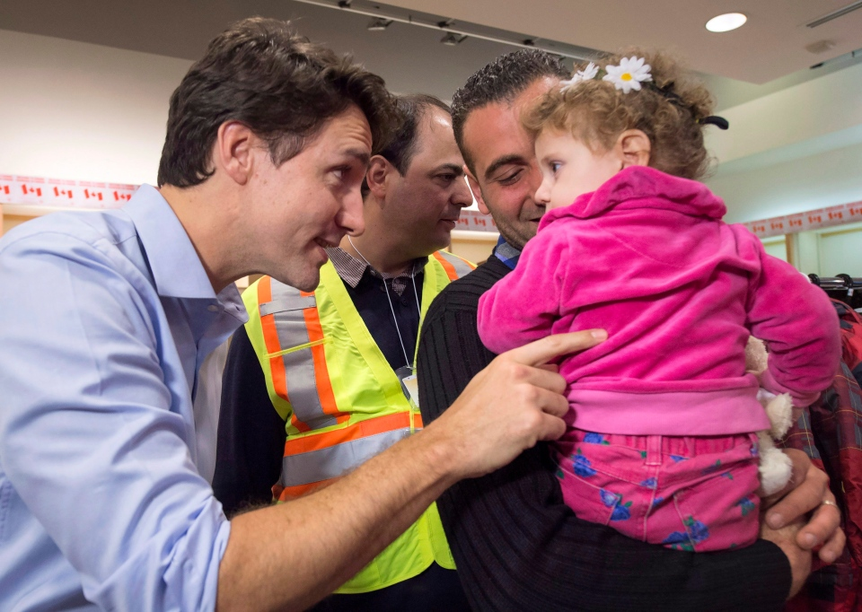 Canadian Prime Minister Justin Trudeau speaks with a young girl as he greets a family of Syrian refugees during their arrival at Pearson International airport, in Toronto, on Dec. 11, 2015. (Nathan Denette / The Canadian Press)