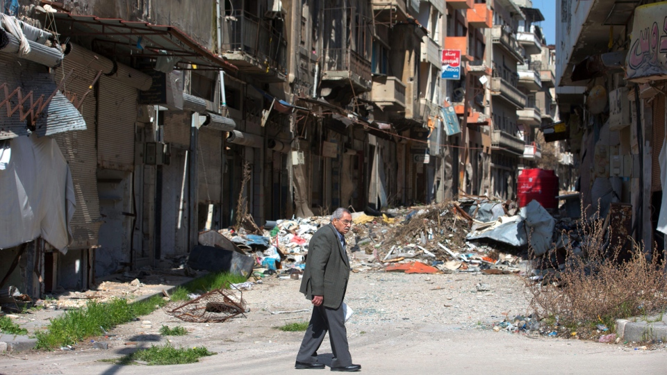 In this picture taken Friday, Feb. 26, 2016, a Syrian man walks through a devastated part of the old city of Homs, Syria. (AP / Hassan Ammar)