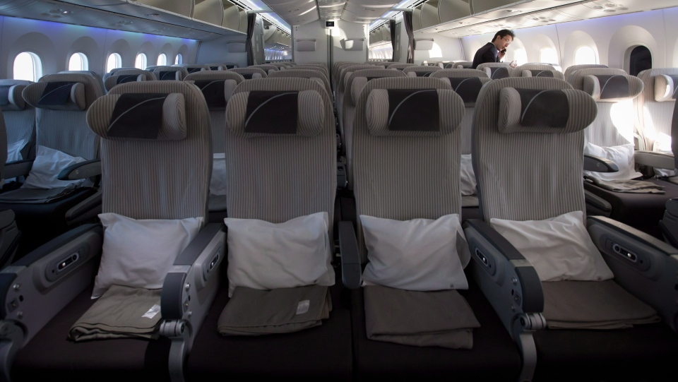 Seats are prepared for a flight as an airline official speaks on a mobile phone in the forward economy cabin of a Japan Airlines Boeing 787-800 Dreamliner after it arrived at Vancouver International Airport in Richmond, B.C., on Monday February 3, 2014. (Darryl Dyck / THE CANADIAN PRESS)