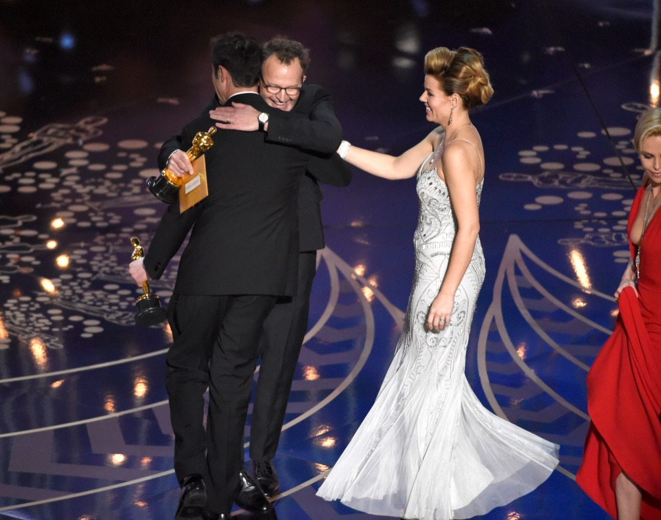 Josh Singer, left, and Tom McCarthy hug on stage after accepting the award for best original screenplay for 'Spotlight' at the Oscars on Sunday, Feb. 28, 2016, at the Dolby Theatre in Los Angeles. (Photo by Chris Pizzello/Invision/AP)