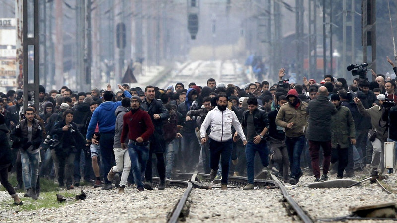 In this photo taken from the Macedonian side stranded refugees and migrants in the northern Greek village of Idomeni approach the Greek-Macedonian border as they try to enter Macedonia on Monday, Feb. 29, 2016. (AP /Boris Grdanoski)