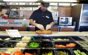 In this March 3, 2015 photo, Roberto Castelan makes a sandwich at a Subway sandwich franchise in Seattle. (AP/Ted S. Warren)