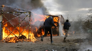 Migrants run past burning tents in a makeshift camp near Calais, France, Monday, Feb. 29, 2016. (AP / Jerome Delay)