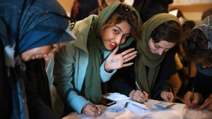 An Iranian voter shows her hand with numbers 30+16, a reformist slogan urging people to vote all reformists and moderate candidates in Tehran, for both parliament and Assembly of Experts elections, as she fills out her ballot in a polling station in Tehran, Iran, Friday, Feb. 26, 2016. (AP / Vahid Salemi)