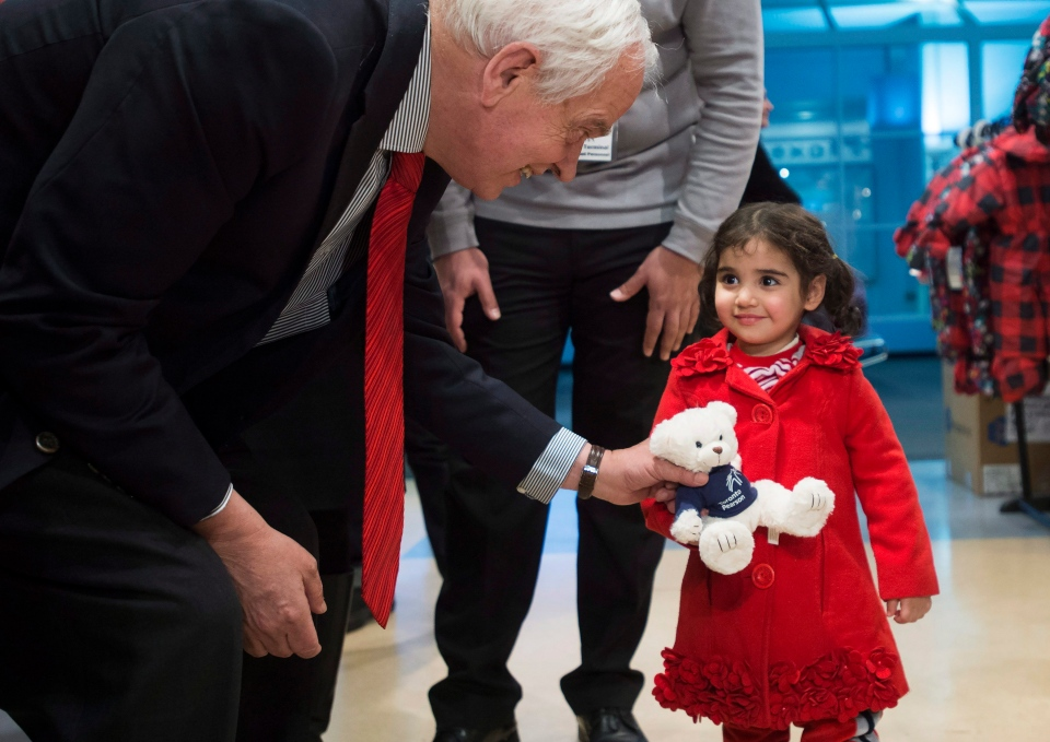 John McCallum, left, Minister of Immigration, Refugees and Citizenship, gives a bear to two-year-old sister Minisa at Pearson International Airport in Toronto on Monday, Feb. 29, 2016. (Nathan Denette / THE CANADIAN PRESS)