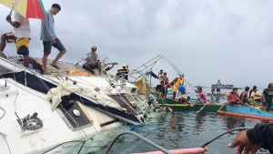 Police, coast guard and Filipino fishermen inspect a yacht near the shore off Barobo township, Surigao Del Sur province in southeastern Philippines on Saturday Feb.27, 2016. (Christopher Templanza / PNP Barobo Station)