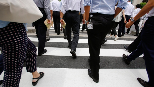 Office workers walk in Tokyo, Japan