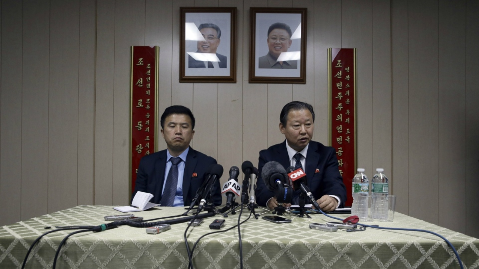 Under the portraits of the late North Korean leaders, Kim Il Sung, left, and Kim Jong Il, ambassador of the Permanent Mission of the Democratic People's Republic of Korea to the United Nations Jang Il Hun, right, is joined by councilor Kwon Jong Gun as he speaks during a news conference at the DPRK mission in New York on July 28, 2015. (AP / Mary Altaffer)