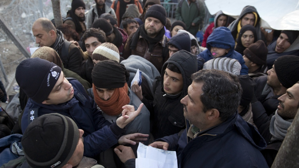 A Greek police officer checks registration papers as refugees crowd to cross the border from the Greek side to Macedonia at the northern Greek border station of Idomeni, Wednesday, March 2, 2016. (AP / Petros Giannakouris)