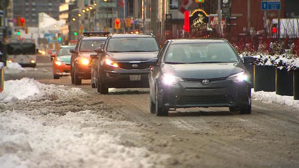 Cars drive down a snowy street in Toronto early Wednesday, March 2, 2016.