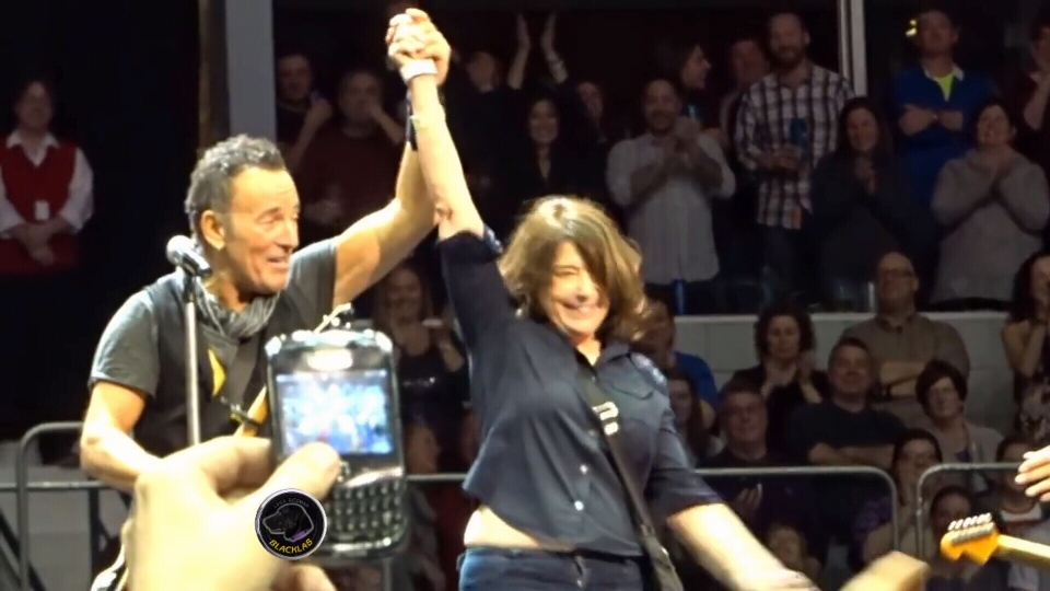 Bruce Springsteen holds up Teri Walderman's hand at a concert in Rochester, N.Y. on Saturday, Feb. 27, 2016.