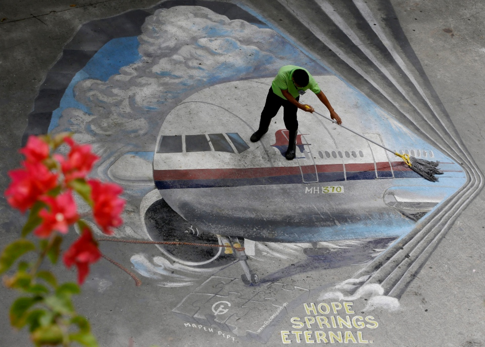 In this April 8, 2014, file photo a school utility worker mops a mural depicting the missing Malaysia Airlines Flight 370 at the Benigno 'Ninoy' Aquino High School campus at Makati city east of Manila, Philippines. (AP / Bullit Marquez)