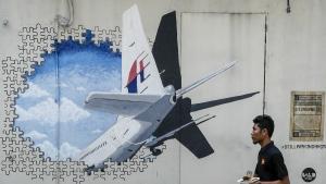 A waiter walks past a mural of flight MH370 in Shah Alam outside Kuala Lumpur, Malaysia on Tuesday, Feb. 23, 2016. (AP / Joshua Paul)