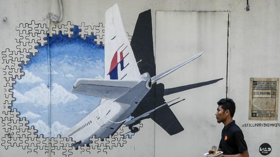 A waiter walks past a mural of flight MH370 in Shah Alam outside Kuala Lumpur, Malaysia on Tuesday, Feb. 23, 2016. (AP / Joshua Paul)