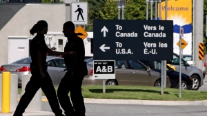 Canadian border guards are silhouetted as they replace each other at an inspection booth at the Douglas border crossing in Surrey, B.C., on August 20, 2009. (Darryl Dyck/The Canadian Press)