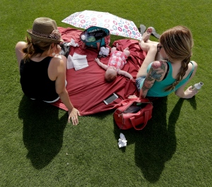 Four-month-old Kyreen Coppinger is shielded from the sun by an umbrella as she attends a spring training baseball game between the Seattle Mariners and the San Diego Padres with her mother Alexis Coppinger, left, and Britteny Skaar Thursday, March 3, 2016, in Peoria, Ariz. (AP Photo/Charlie Riedel)